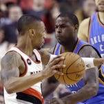 Portland Trail Blazers guard Damian Lillard, left, drives on Oklahoma City Thunder guard Dion Waiters during the first half of an NBA basketball game in Portland, Ore., Friday, Feb. 27, 2015.