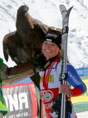 After winning Friday's downhill, Lara Gut (SUI) stands with a 33 year old Golden eagle as they pose for the camera. She won the first women's downhill of the season, at Beaver Creek, Colo.