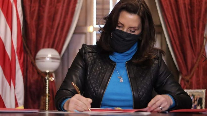 Michigan Gov. Gretchen Whitmer signs the state's latest COVID-19 relief package.