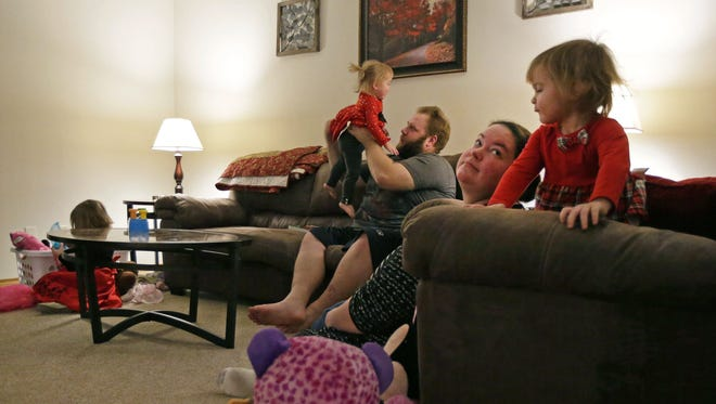 Megann and Andy Hooyman play Tuesday with their children, Callie, Rylee and Zoey, before dinner at the family's temporary home, a duplex in Appleton.