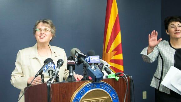 Superintendent Diane Douglas, left, talks to media