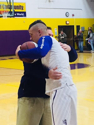Lexington junior Cade Stover receives a hug from coach Scott Hamilton while being honored for joining the 1,000 Point Club prior to Friday's home game with Madison.
