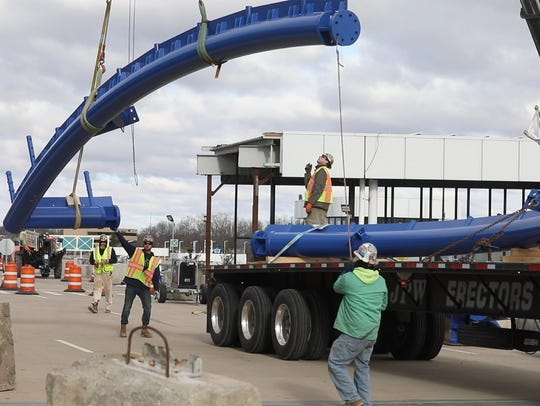 Workers unload steel rods for the new airport canopy.