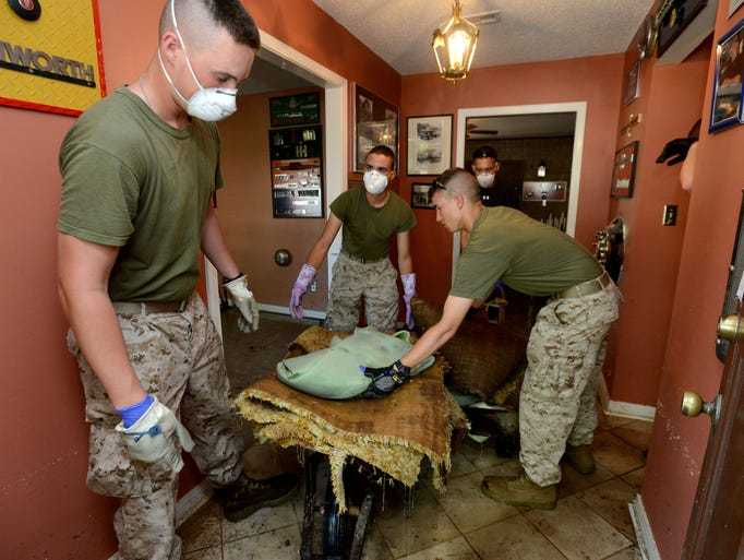 Students from Marine Aviation Training Support Group 21 (MATSG-21) remove soggy carpet from a home on Dracena Way in Gulf Breeze on Wednesday as part of a volunteer effort coordinated at the Gulf Breeze United Methodist Church.