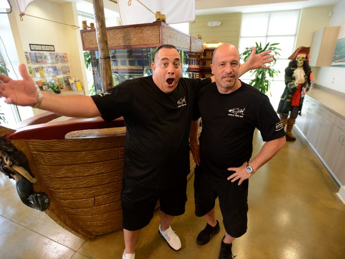 Aquarium creators Wayde King, left, and Brett Raymer, from Acrylic Tank Manufacturing and Animal Planet's series Tanked, have their photo taken in front of the finished aquarium Friday that was custom built and delivered for the Perdido Key Area Chamber of Commerce. The delivery and set up of the aqaurium will be featured on an episode of Tanked. The 400 gallon was funded by a BP grant and will feature nearly 50 local and non-native fish.