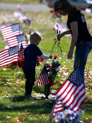 Bodie Rector, 3, and Mary Price place a carnation at a gravesite during a ceremony honoring veterans on Friday at Memory Gardens Cemetery in Farmington.