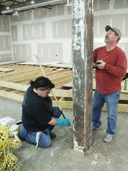 Diane Jewell and Neal Porter scrap old glue off a support beam in the room that will become the sanctuary of Lafayette Community Church.