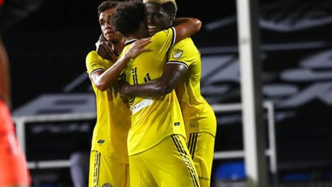 Columbus Crew SC striker Gyasi Zardes (11) celebrates with teammates after scoring a goal against FC Cincinnati during the first half of their Saturday night match in the MLS Is Back tournament in Orlando.