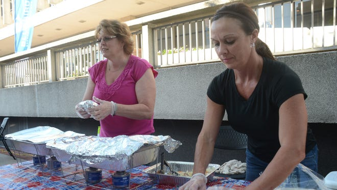 Hot Chicks BBQ owner Tammy Gilchrist (right) makes a pork and cole slaw wrap as Denise Good takes an order at Dinner on the Bricks Thursday in downtown Alexandria. Hot Chicks BBQ was among the food vendors participating in Dinner on the Bricks in downtown Alexandria.