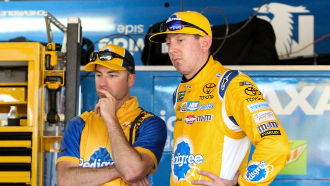 Kyle Busch, right, and crew chief Adam Stevens, left, stand in the garage at Dover International Speedway.