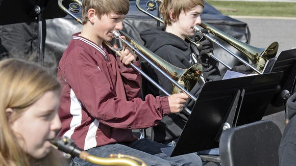 Members of the Asheville Middle School jazz band, including Jackson Hunter on trombone in center, performed at the finish line of the Asheville High School Band-Aid 5K and 8K. More than 100 runners took part in the 5K, 8K and Fun Run in an effort to raise money to, among other things, help replace old and aging instruments for the Asheville High band last year.