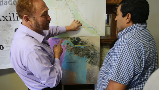 Immigration attorney Carlos Spector, left, and Martín Huéramo, of Mexicans in Exile, look over a map of the land near the Tornillo-Guadalupe international bridge. Huéramo's group claims authorities are threatening and extorting owners of land near the new bridge because of its high value.