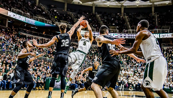 Bryn Forbes hits a fall-away jumper over Thomas Bruce of Binghamton in the first half of their game Saturday in East Lansing.