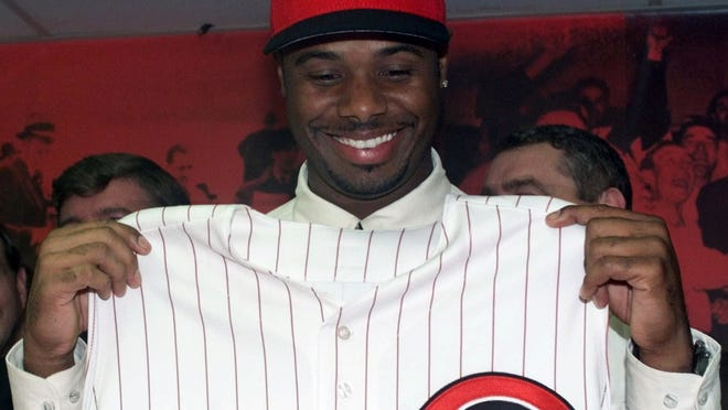 Ken Griffey Jr. holds up a Reds jersey on Feb. 10, 2000, after his trade from the Seattle Mariners was announced.