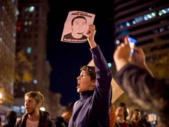 A protester chants in Oakland, Calif., on Tuesday, Nov. 25, 2014, a day after the announcement that a grand jury decided not to indict Ferguson police officer Darren Wilson in the fatal shooting of Michael Brown.