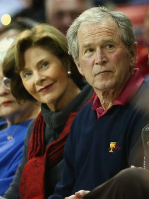 Former President George W. Bush and his wife, Laura, attend a game between the Illinois-Chicago Flames and the Southern Methodist Mustangs at Moody Coliseum on Dec. 17, 2014 in Dallas.