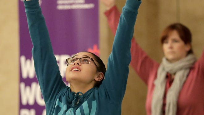 Olivia Bauer-Shimek, a student at Menasha High School, takes part in a Yoga tutorial during the United Way Fox Cities' Teen Symposium on Monday at the Radisson Paper Valley Hotel in Appleton. Wm. Glasheen/USA TODAY NETWORK-Wisconsin
