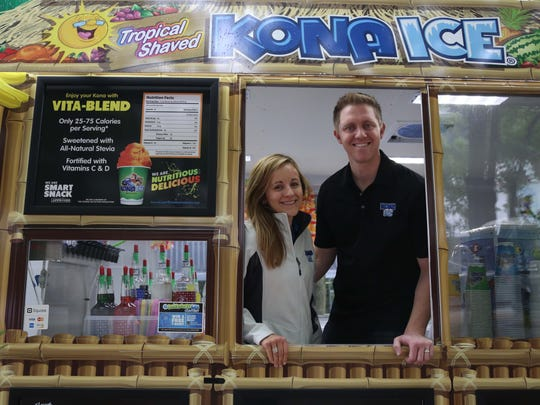 Steve and Brooke Bensema of Ames stand inside the Kona Ice shaved ice truck that they own and operate.