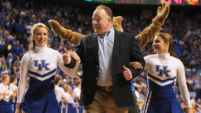Kentucky football coach Mark Stoops was led off the court by two cheerleaders after he greeted the crowd and helped form the letter Y of Kentucky during a timeout at Rupp Arena Saturday.