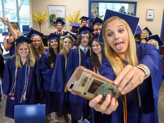 Graduate Sophia Siegel takes a group selfie with her