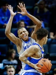 University of Memphis forward Jimario Rivers (back) applies defensive pressure to McNeese guard Kalob Ledoux (front) during first half action at the FedExForum.