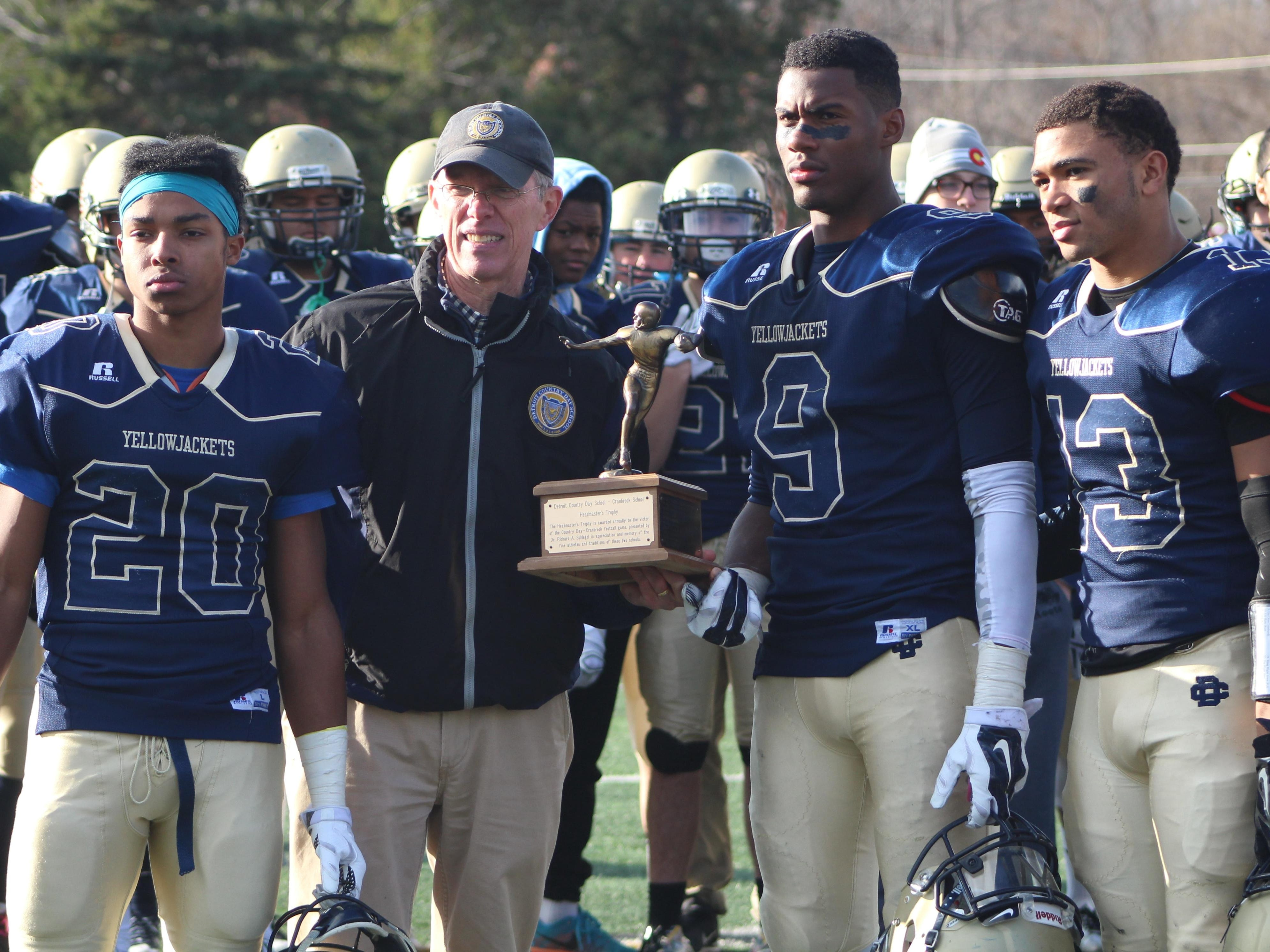 Detroit Country Day players (from left) Larry Penson, Jeremiah Tyler and Steve Mann, along with Headmaster Glen Shilling, accept the Division 4 regional championship trophy.