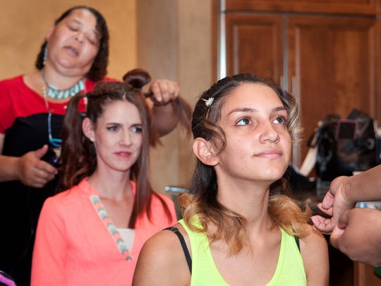 Models Gabby Caffaro, foreground, and Kimberley Rey, background, get their hair done by Linda Haywood, and Vanessa Scott, not pictured, in preparation for their photo shoot.