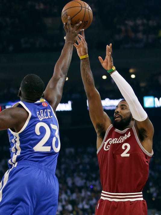 Cleveland Cavaliers' Kyrie Irving (2) has his shot blocked by Golden State Warriors' Draymond Green (23) during the first half of an NBA basketball game Friday, Dec. 25, 2015, in Oakland, Calif. (AP Photo/Marcio Jose Sanchez)