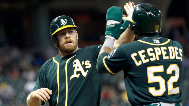 Oakland Athletics' Brandon Moss, left, and Yoenis Cespedes celebrate after scoring on Josh Donaldson's double during the ninth inning of a baseball game against the Houston Astros.