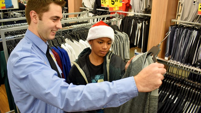Novi's Zakaria Jallow shops with Wixom Police Service Aid Officer Andrew Tabor.