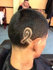 A former student of Kate Madigan shaved a breast cancer ribbon into his hair in honor of her year-long treatment.