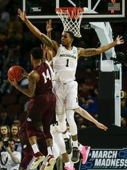 Michigan guard Charles Matthews tries to block a shot