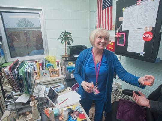 Nurse Patti Butler gives medicine to a student during
