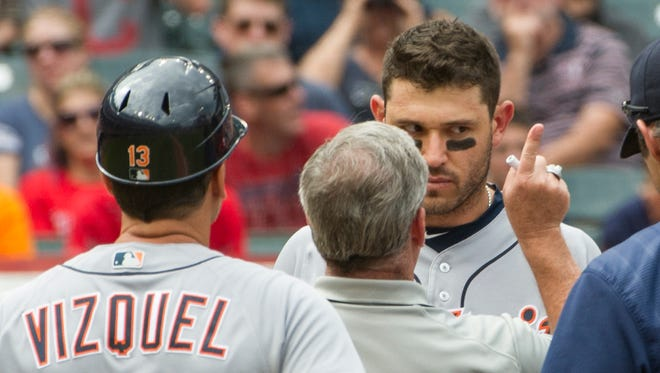 Detroit Tigers' Ian Kinsler is checked by a trainer after being hit in the head by Cleveland Indians starting pitcher Trevor Bauer during the third inning Sunday.