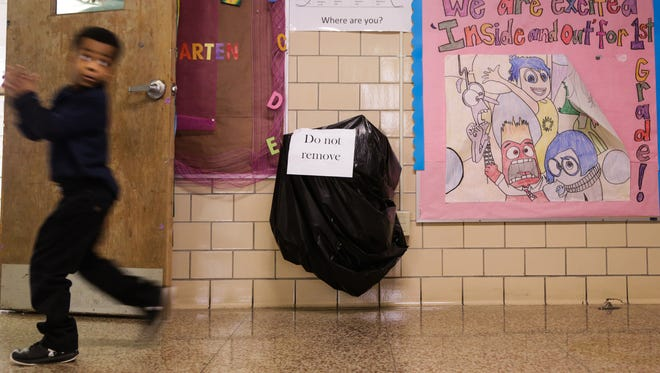 A student walks past a drinking fountain covered in a bag to stop students from drinking due to the Flint water crisis during the school day at Northridge Academy charter school in Flint on Thursday February 4, 2016. Tens of thousands of Flint children who were exposed to lead during the Flint water crisis will be screened to determine whether they need health or special education services, under an unprecedented partial settlement of a federal lawsuit against the state and two school districts.