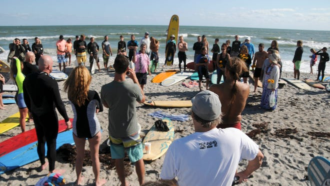 Friends and family of Dana Brown gather on the beach at Murkshe Park in Cocoa Beach for a memorial paddle out.