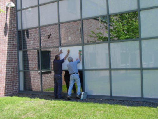 Workers place film on reflective glass panels at a
