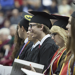 Graduates eagerly await the awarding of their degrees.