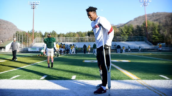 Reynolds senior Dre Dowdle laughs as he walks along the sidelines with his crutches during practice Wednesday, Nov. 29, 2017. Dowdle broke his leg in a game against Roberson at the end of the regular season. He now has to encourage the Rockets, who are two games away from a state title, from the sidelines.