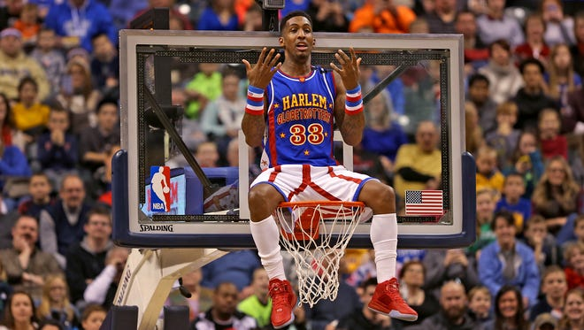 Harlem Globetrotter Bull Bullard goofs around on the rim during last year's game at Bankers Life Fieldhouse, The Globetrotters return to the fieldhouse on Jan. 14.