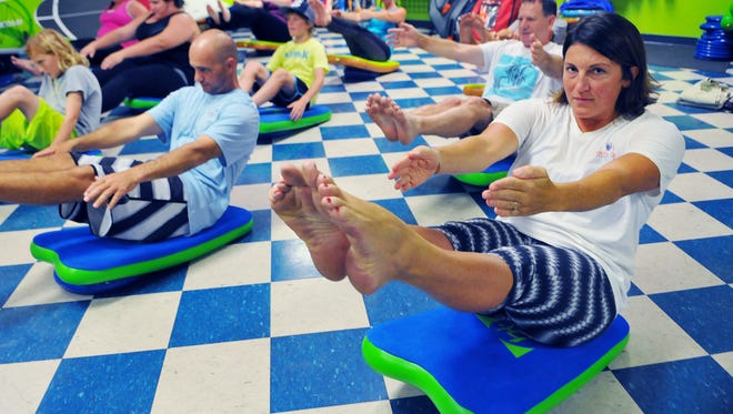 Florida Today's Michelle Mulak fitness & water reporter try's her hand at I FIT (Inflatable Fitness Balance Board) during Wednesday night Fitness class held at Paddling Paradise in  Melbourne, taught by Kat Bartlett of Melbourne Fitness on Air and Sup Yoga Instructor.