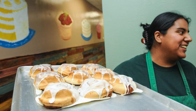 Green Door Bakery and Cafe owner Elena Tirre holds a tray of freashly baked cinnamon buns on Thursday.