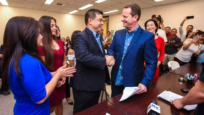 Lt. Gov. Ray Tenorio, right, and running mate, Sen. Tony Ada, shake hands after submitting organizational documents to the Guam Election Commission in Hagåtña on Thursday, Jan. 18, 2018. With family and supporters at their side, both Tenorio and Ada officially announced their intention to seek the office of the governor in this year's upcoming gubernatorial election.
