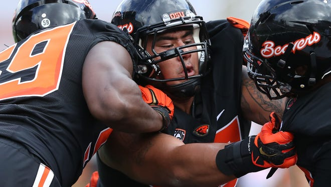 Oregon State defensive tackle Kyle Peko, center, collides with teammates during the first day of fall practice on Saturday, Aug. 8, 2015, in Corvallis, Ore.