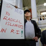 Howard Brown, of North Kingstown, R.I., center, displays a placard during a rally Thursday at the statehouse in Providence, R.I., held to demonstrate against allowing Syrian refugees to enter the state following the terror attacks in Paris.