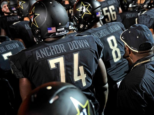 Vanderbilt players walk back to the locker room with Coach Derek Mason due to the weather at Vanderbilt Stadium in Nashville, Tenn., Thursday, Aug. 28, 2014.