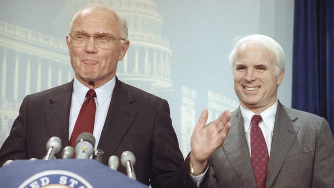 """Sen. John Glenn (left), D-Ohio, and Sen. John McCain, R-Ariz., smile on Oct. 23, 1990, during a news conference on Capitol Hill in Washington. A special counsel for the Senate Ethics Committee recommended dismissal of the cases against the two senators for their involvement in the """"Keating Five"""" investigation."""
