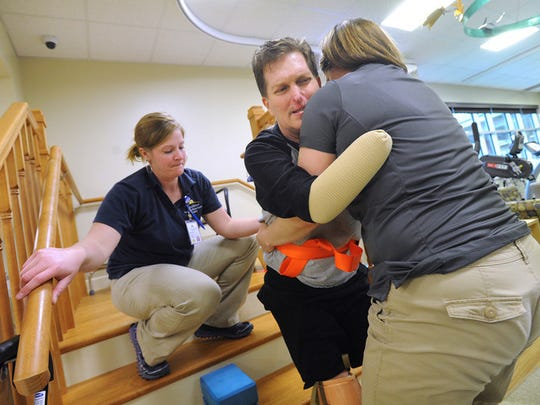 WellSpan physical therapist Jenny Reimold, right and occupational therapist Alicia Fry, left, help Paul Miller navigate getting up stairs during one of Miller's therapy sessions at WellSpan Surgery &  Rehabilitation Hospital on Friday, April 12, 2013. Miller was struck with Streptococcus Pneumoniae on Sunday, Feb 3, 2013, resulting in the amputation of his hands and feet. Jason Plotkin - Daily Record/Sunday News