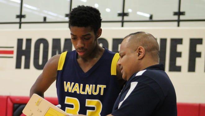 Walnut Hills coach Ricardo Hill gives senior Jordan Henderson the play against Elder March 3.