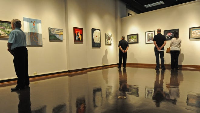 People are pictured looking at art on display at the Louisiana State Exhibit Museum in Shreveport. The museum was one of 14 state-run museums facing cuts but is working out a deal to operate at its current levels until the end of fiscal year 2015.